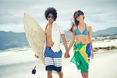 Brasil latino hispanic couple walking holding hands with surfboard and flag as sarong