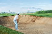 stock photo of hazardous  - golf shot from sand bunker golfer hitting ball from hazard - JPG