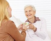 Family with senior woman drinking coffee in a retirement home