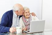 Man kissing happy senior woman at the computer on the cheek