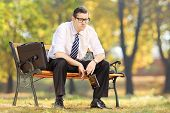 Disappointed businessman sitting on a wooden bench with bottle in his hand, in park