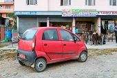 Pokhara, Nepal - NOVEMBER 21, 2013: Red Tata Nano. The Tata Nano is the cheapest car in the world with a price starting at around $2000 in India.