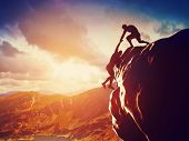 picture of strength  - Hikers climbing on rock - JPG