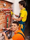 Men builder fixing heating system with special tool.