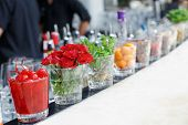 Cocktail cherries, herbs and rose flowers on bar counter