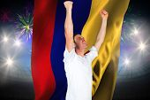Cheering football fan in white against fireworks exploding over football stadium and colombia flag