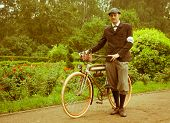 Man posing with retro bicycle in the park. Vintage style.