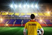 Colombia football player holding ball against stadium full of colombia football fans