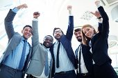 Group of ecstatic business partners looking at camera with raised arms