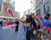 Parade watchers wave flags from behind barriers