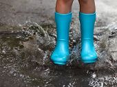picture of rain  - Child wearing blue rain boots jumping into a puddle - JPG