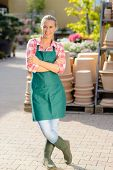 Garden center woman worker with apron standing with arms crossed