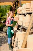 Garden center woman worker make inventory of clay pots sunny
