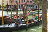 Gondolier Photographs Tourists Sitting In A Gondola, Venice, Italy