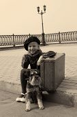 little girl sitting on the road with a dog and a suitcase