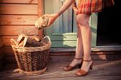 Woman On Porch Getting Logs For Firewood