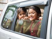 Asian Indian family going to a vacation. Happy children sitting inside car with window open looking