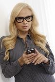 Beautiful blonde woman using mobilephone, wearing black framed glasses.