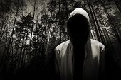 stock photo of dangerous  - Portrait of dangerous man hiding under the hood in the forest - JPG