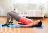 fitness, home and diet concept - smiling teenage girl doing exercise for legs and buttocks on floor