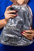Young woman with fashion red nails holding silver sequin backpack bag