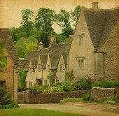 Bibury in spring. Traditional Cotswold cottages in England, UK. Photo in retro style. Paper texture.