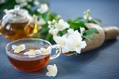 picture of jasmine  - jasmine tea in a teapot with a branch of jasmine on a wooden table - JPG