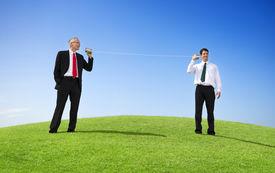 stock photo of tin man  - Business Men Outdoors Talking Through Tin Can Phone - JPG
