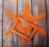 Sun shaped lentil and wooden frame on wooden background