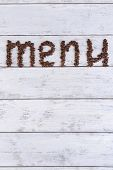 Inscription menu of coffee beans on table close-up