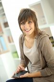 Smiling girl sending text message on smartphone