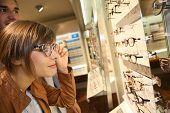 Young woman in optical shop trying eyeglasses on