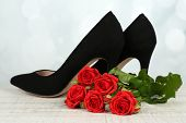 Beautiful woman shoes with flowers on bright background