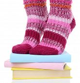 Girl in colorful socks standing on pile of books isolated on white