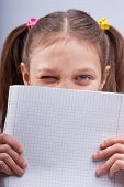 Little Girl Winking Behind A Squared Exercise Book