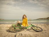 A girl at the beach with her bike