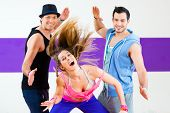 foto of zumba  - Group of men and women dancing zumba fitness choreography in dance school - JPG