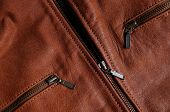pic of nylons  - Main zipper and front pockets zippers of a brown leather jacket showing nylon seams - JPG