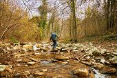 Hiker Man Crossing A River On Stones