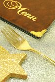 Golden fork and restaurant menu on festive background
