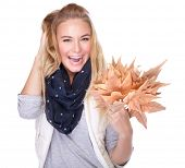 Portrait of nice happy girl with dry maple leaves in hand isolated on white background, enjoying beautiful autumn bouquet