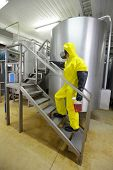 technician in protective coveralls with sample of fluid in plastic container walking up the stairs in laboratory