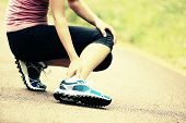 stock photo of pain-tree  - young woman runner hold her twisted ankle - JPG