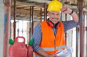 Portrait Of Confident Male Architect With Blueprint At Construction Site