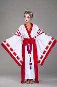 Beautiful young woman in white kimono dress on gray background