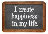 I create happiness in my life - positive affirmation words on a vintage slate blackboard