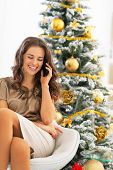 Portrait Of Happy Young Woman Talking Cell Phone Near Christmas