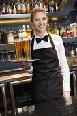 Pretty waitress holding a tray of champagne in a bar