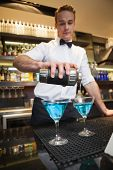 Bartender pouring cocktail into glasses in a bar