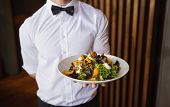 Waiter showing plate of salad to camera in a bar